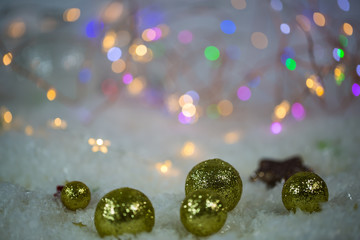 Christmas tree balls in the snow, lights in the background