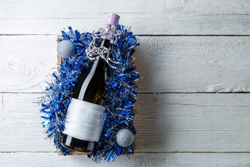 Photo of bottle of wine with blank card in box with tinsel,