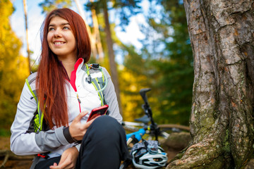 Image of happy woman with cellular phone in autumn forest