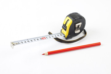 Black tape-measure with red pencil on a white background.