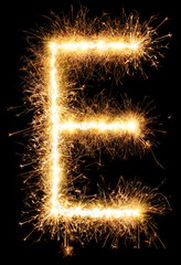 Sparkler firework light alphabet E isolated on black