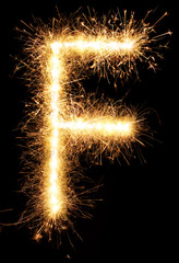 Sparkler firework light alphabet F isolated on black