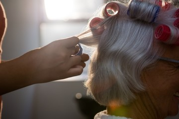 Hands of hairstylist removing curlers from senior woman hair