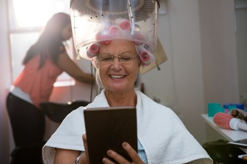 Senior woman using digital tablet while sitting under hair