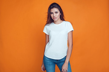 Sexy woman in a white T-shirt on the orange background. Mock-up.