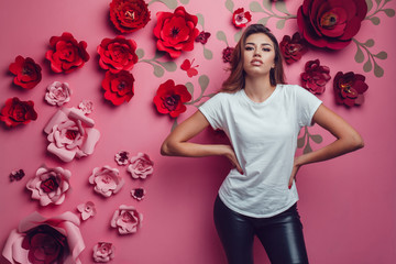 Sexy woman in a white t-shirt on a pink background with flowers.