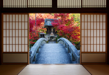 Bridge and autumn trees seen through the open doors of an old Japanese dojo