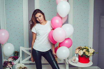 Attractive girl in a white t-shirt holds balloons. Mock-up.