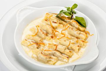 Close-up of the bowl of ravioli bowl of ravioli in white sauce with grated orange peel.