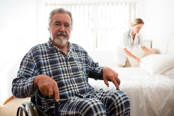 Portrait of senior man sitting on wheelchair while doctor