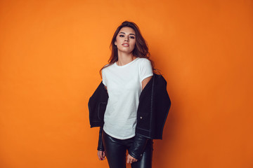 Wall Mural - Sexy woman in white t-shirt and jacket on the orange background. Mock-up.