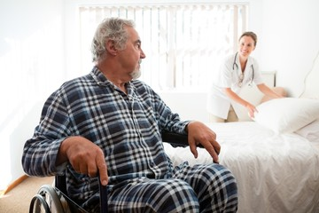 Senior man looking at doctor adjusting bed while sitting on