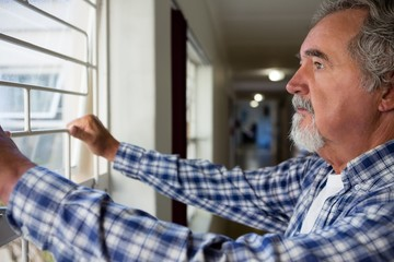 Thoughtful senior man looking through window at retirement home