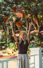 Beautiful blonde woman in straw hat throws up dry leaves. Wears a black t-shirt and white long skirt. Autumn in Thailand. Hands with tattoos.