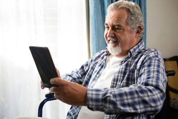 Smiling senior man using digital tablet by sitting on wheelchair