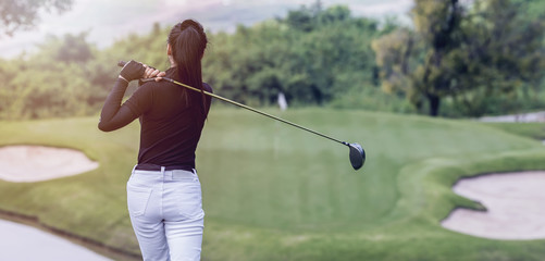 Stores à enrouleur Golf Young women player golf swing shot on course