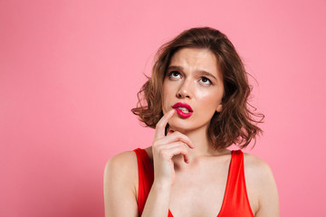 Close-up portrait of thinking young beautiful woman with red lips, touching with finger her cheek, looking upward