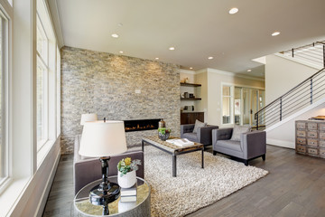 Modern great room with a floor to ceiling stone fireplace