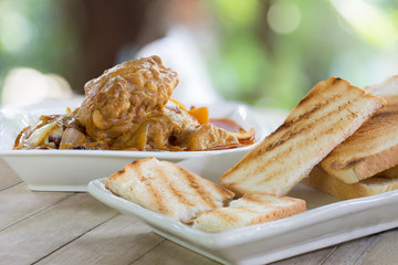 Grill bread eat with Mussaman curry chicken in white bowl on old wooden table