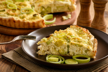 Quiche with leek and cheese on brown background.
