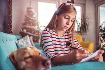 Girl with dog writing wish list on sofa