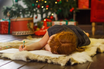 Red-haired girl near the Christmas tree writes a letter to Santa