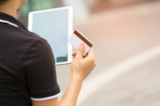Close up of Man Hands holding credit card and using Tablet,Online shopping concept