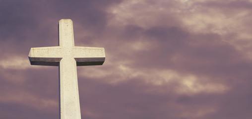 Kreuz vor wolkigem Himmel