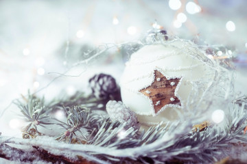 Christmas Still Life  -  Natural decoration with white christmas bauble and fir branch on snow background  -  Greeting card
