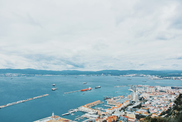 Aerial view to a port, blue vivid sea ocean lake water and mountains at the background on cloudy day.
