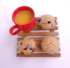 A cup of orange juice and muffins with black currant