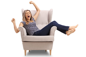 Tired young woman lying in an armchair and yawning