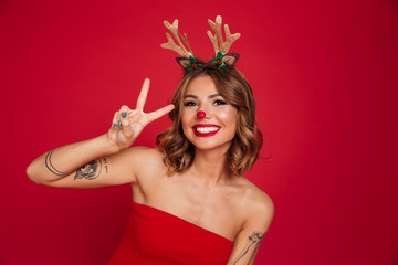 Portrait of a smiling attractive girl wearing christmas deer costume Fototapete