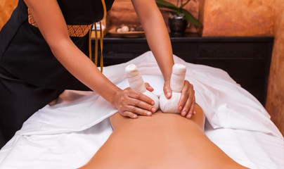 Woman getting thai herbal ball massage treatments in spa.