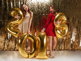 Full length portrait of two beautiful cheerful girls