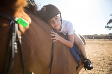 Portrait of cute girl embracing horse in the ranch