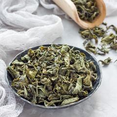Dry green tea leaves on metal plate, square