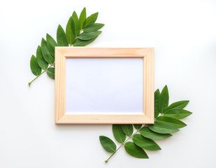 Empty wooden photo frame mock-up with green leaves around, isolated on white background.