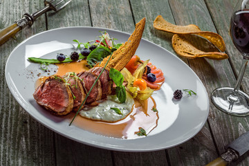 Plate with medium rare meat steak, sauce and salad on a wooden table. Healthy gourmet food made of meat fillet and fresh vegetables.