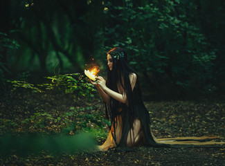 A fabulous, forest nymph with long hair found a flaming, fiery flower, with which little butterflies and fairies fly out. Artistic Photography
