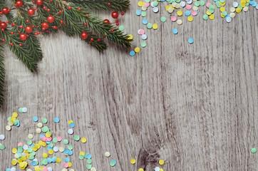 Fir branch and multi-colored confetti.