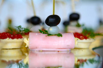 Canapes with meat rolls and Tartlets with red caviar on holiday table. Luxurious finger food. Snacks for the party.