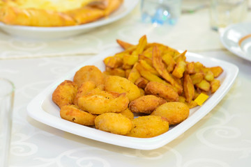 Fries served on a platter. Fried potatoes in a restaurant. Unhealthy but satisfying food.