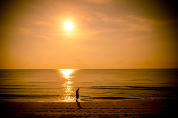 Golden sun set in tropical hot summer beach in thailand with unidentified person in background,