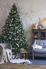 Big beautiful Christmas tree is decorated with Scandinavian interior