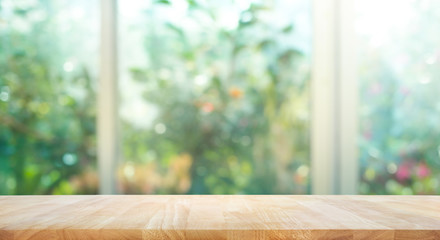 Wood table top on blur of window with garden flower background in morning.For montage product display or key visual layout.