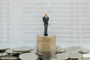 Money, Financial, Business Growth concept, Businessman miniature figure stand on stack of silver coins with bank passbook as background.