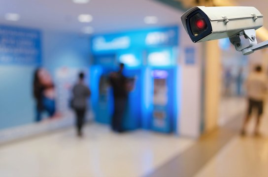 CCTV, security indoor camera system operating with blurred image of people queuing to withdraw money from ATM banking machine, surveillance security and safety technology concept