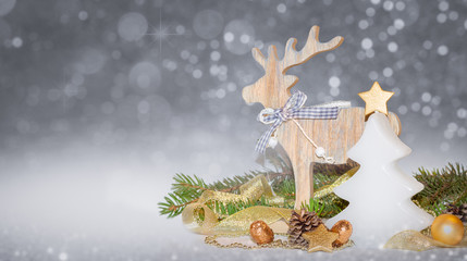 Christmas gold, white decoration, ornaments with tree shaped candle,baubles, reindeer on a silver background with blurred, bokeh lights