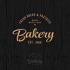The bakery logo. Bread and baking emblem. Vintage bakery logo. Gold inscription on a dark tree.